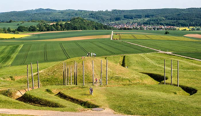 Tumulo della necropoli celtica di Glauberg. Davanti al colle funerario sono visibili i pali che costituirebbero un calendario astronomico. Ricostruzione. Intorno al tumulo si vede il largo fossato interrotto dalla via processionale. foto-E-W CC BY-SA 3.0